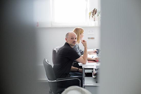 zwei Mitarbeitende beim gemeinsamen Pruefen einer Bewerbung, ein Mitarbeiter schaut dabei aus den Tuerspalt