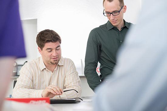 zwei Mitarbeiter schauen gemeinsam auf eine Bewerbung
