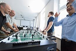 Vier Mitarbeiter spielen Kicker und freuen sich
