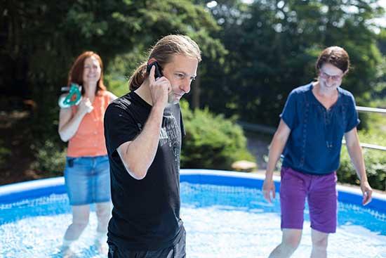 drei Mitarbeitende stehen im Pool, zwei davon laecheln und ein Mitarbeiter telefoniert