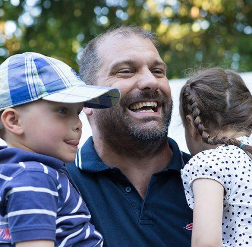 Mitarbeiter mit seinen Kindern auf dem Arm